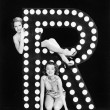 Two young women posing with the letter R — Stok fotoğraf