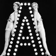 Two young women posing with the letter A — Stock Photo
