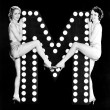 Two young women posing with the letter M — Stockfoto