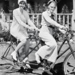 Portrait of two young women sitting on a tandem bicycle - Foto de Stock  