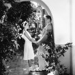 Profile of a couple romancing in an archway - Stock Photo