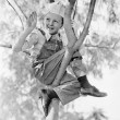Low angle view of a boy sitting on a tree - Foto de Stock  