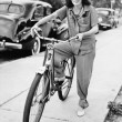 Portrait of a young woman holding a bicycle and smiling — Foto de Stock