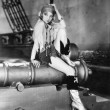 Profile of a young woman sitting on a cannon and thinking — Stock Photo