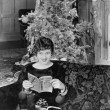 Young woman sitting on a couch with a Christmas tree in the background — Stock fotografie