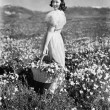 Rear view of a girl standing in a meadow holding a flower basket and smiling - Foto de Stock  