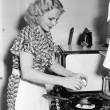 Young woman breaking an egg into a frying pan — Stock Photo