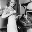 Young woman basting a goose in the kitchen — Stock Photo