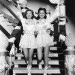 Two young women stepping down a staircase waving their western hats - Foto Stock