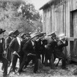 Group of men with guns and top hats breaking into a barn - Foto de Stock  