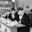 Three men with hats eating at the counter of a diner - Stock Photo