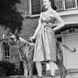 Young woman standing with her Great Dane in a courtyard — Stock Photo #12295107