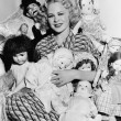Portrait of a woman surrounded by dolls and smiling — Stock fotografie