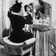 Woman putting on a hat in front of a dressing table - Стоковая фотография