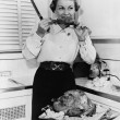 Foto Stock: Womeating roast turkey in her kitchen with knife in her hand