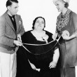 Male tailor and his assistant measuring an overweight woman with a measuring tape — Stock Photo