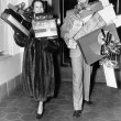Couple walking and holding stacks of presents — Photo