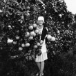 Portrait of a young woman holding grapefruits and standing in an orchard — Stock fotografie