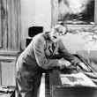 Man shouting with his hand caught in a piano — Stockfoto