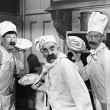 Three chefs holding pies for a fight in the kitchen - Foto Stock