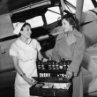 Female nurse with a young woman standing in front of an airplane and opening a medicine box - Стоковая фотография