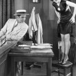 Young woman standing on a chair with a young man looking at her legs - Stock Photo