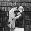 Stock Photo: Profile of a young man attaching a brooch on a young woman's overcoat in a library
