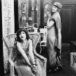 Woman sitting in an armchair with another woman smoking a cigarette in the background - Stock Photo