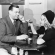 Profile of a man with a young woman smoking sitting in a cafe — Foto de Stock
