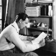 Profile of a young man reading a paper at his desk - Foto Stock