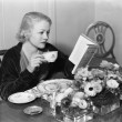 Young woman sitting at the dining table holding a cup of tea and reading a book - Stockfoto