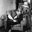 Profile of a man sitting in an armchair and reading a book - Zdjęcie stockowe
