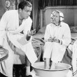 Young man talking to a senior man sitting with his feet soaked in a washtub — Stock Photo