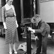 Profile of a man measuring weight of a woman standing on a weighing scale in front of a train — Stock Photo #12296049