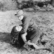 Foto Stock: Young man holding an unconscious young woman