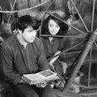 Young man reading a book and a young woman sitting beside him - Stock fotografie