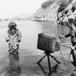 Profile of a young man holding a camera with a scuba diver standing in front of him on the beach — Stock Photo #12296244