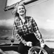 Young woman standing at the helm of a sailboat and holding the wheel — Foto de Stock