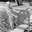Young woman climbing up the ladder of a swimming pool — Stockfoto