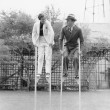 Couple walking on stilts — Stock Photo