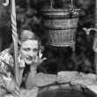 Portrait of a woman leaning on a well with her finger crossed — ストック写真