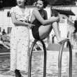 Profile of a young woman sitting on a ladder at the pool side with another woman standing behind her — Stock Photo