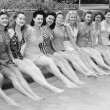 Group of women sitting in a row at the pool side — Stock Photo