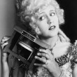 Portrait of a young woman holding one of the first telephones — Stock Photo #12296526