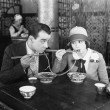 Couple sharing noodle in restaurant — Zdjęcie stockowe #12296626