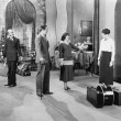 Four standing in a the lobby of a hotel with luggage - Stock Photo