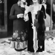 Two women in the street reading papers being thrown down from an office — Stockfoto