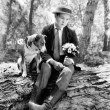 Young man sitting in the woods with his dog looking forlorn — ストック写真