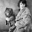 Woman in her fur coat sitting with her dog — Stock Photo