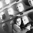Woman looking frightened holding onto one mask on the wall of masks — Foto de Stock